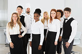 Portrait Of Confident Restaurant Staff Standing Against White Background
