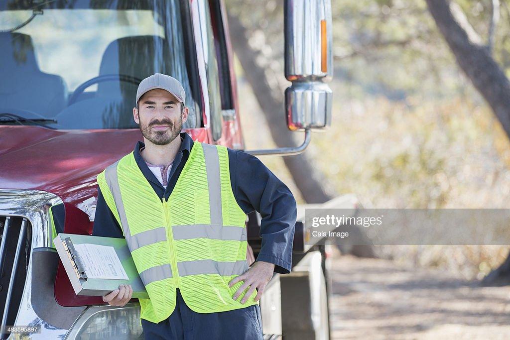 Portrait of confident roadside mechanic leaning on truck