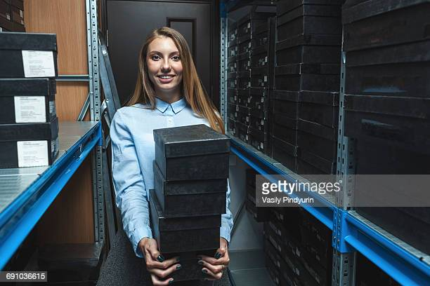 Portrait of confident saleswoman holding stacked shoe boxes in store