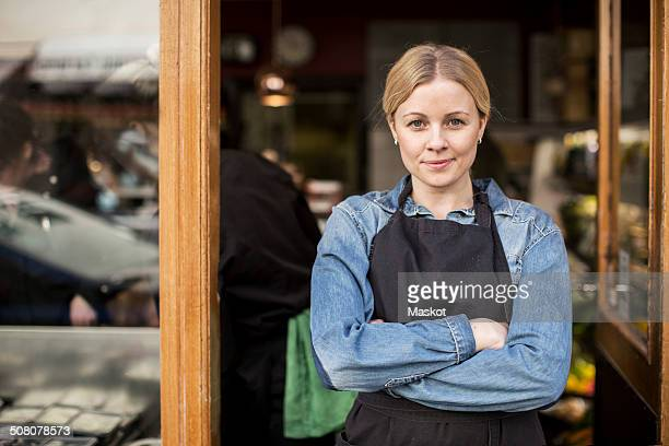 Portrait of confident saleswoman standing arms crossed at supermarket entrance