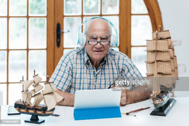 Portrait of confident senior man wearing headphones with tablet and model ship on table