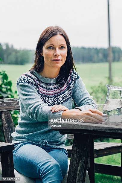 Portrait of confident woman sitting at table in organic farm