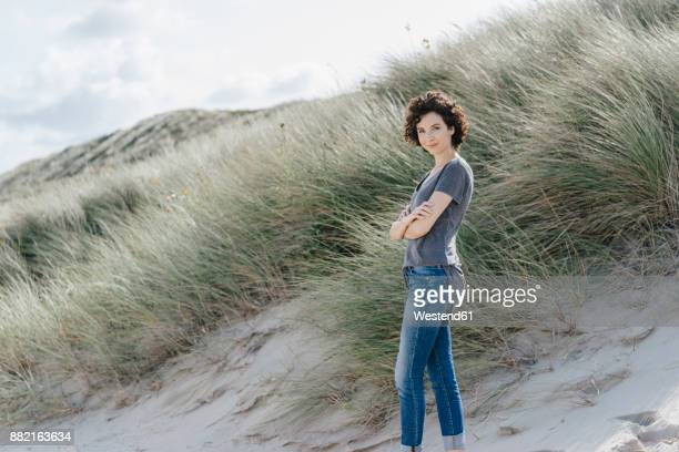 Portrait of confident woman standing in beach dune