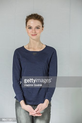 Portrait of confident woman standing with hands clasped against white background