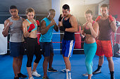 Portrait of confident young boxers ready to fight position standing in boxing ring