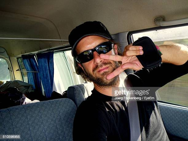 Portrait of confident young man showing victory sign in vehicle
