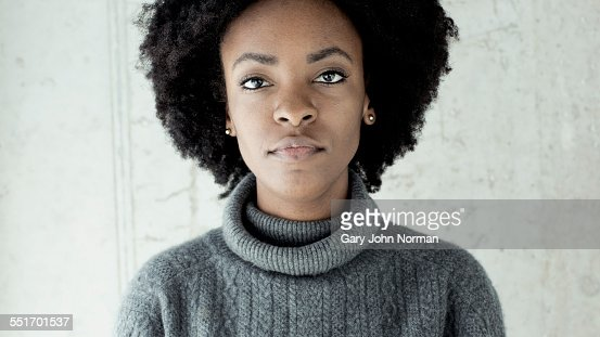 Portrait of confident young woman in front of wall