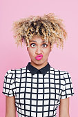Studio portrait of confused afro american young woman staring at the camera. Pink background.