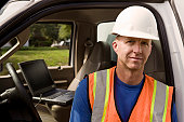 Portrait of construction worker, open truck with laptop in background