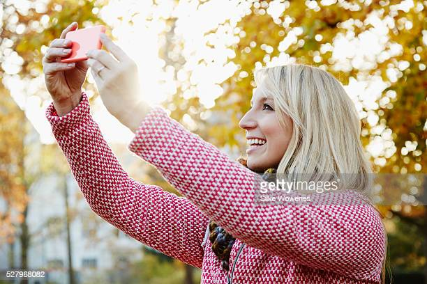 portrait of content adult woman in a park in autumn with smartphone