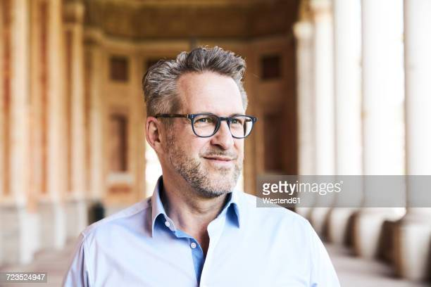 Portrait of content businessman with stubble wearing glasses