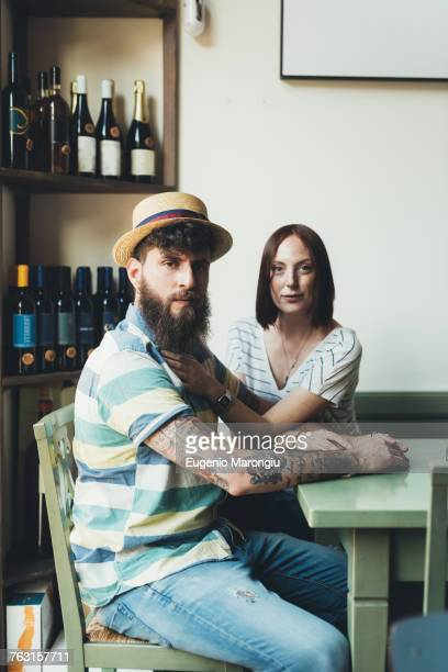 Portrait of cool couple at bar table