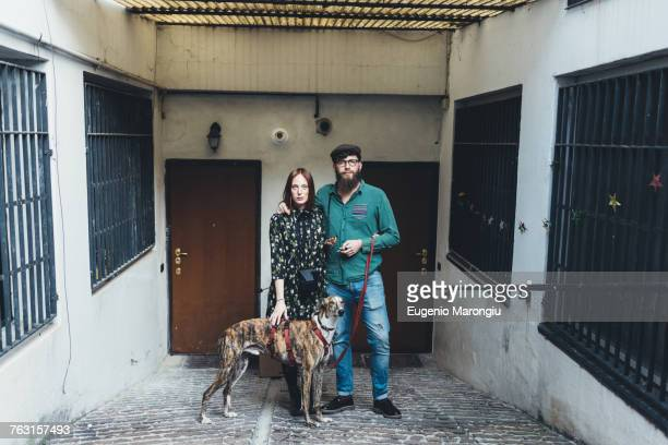 Portrait of cool couple with dog outside apartment