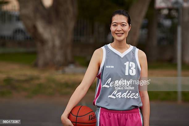 Portrait of cool female basket player holding ball