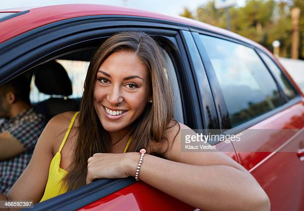 Portrait of cool girl sitting in red car