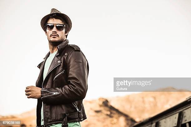 Portrait of cool man wearing leather jacket and shades on rural railway bridge, Franschhoek, South Africa