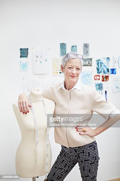 Portrait of cool senior female fashion designer with arm around tailors dummy