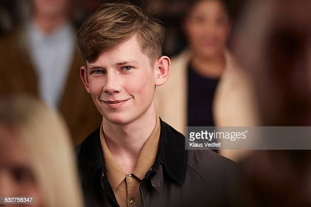 Portrait of cool young man smiling in crowd