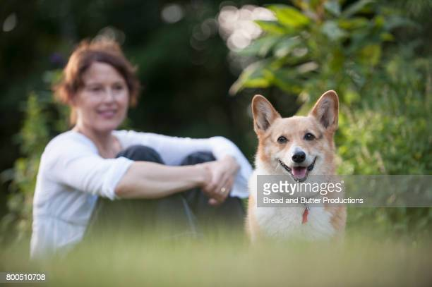 Portrait of Corgi Dog with Smiling Woman sitting on grass in background
