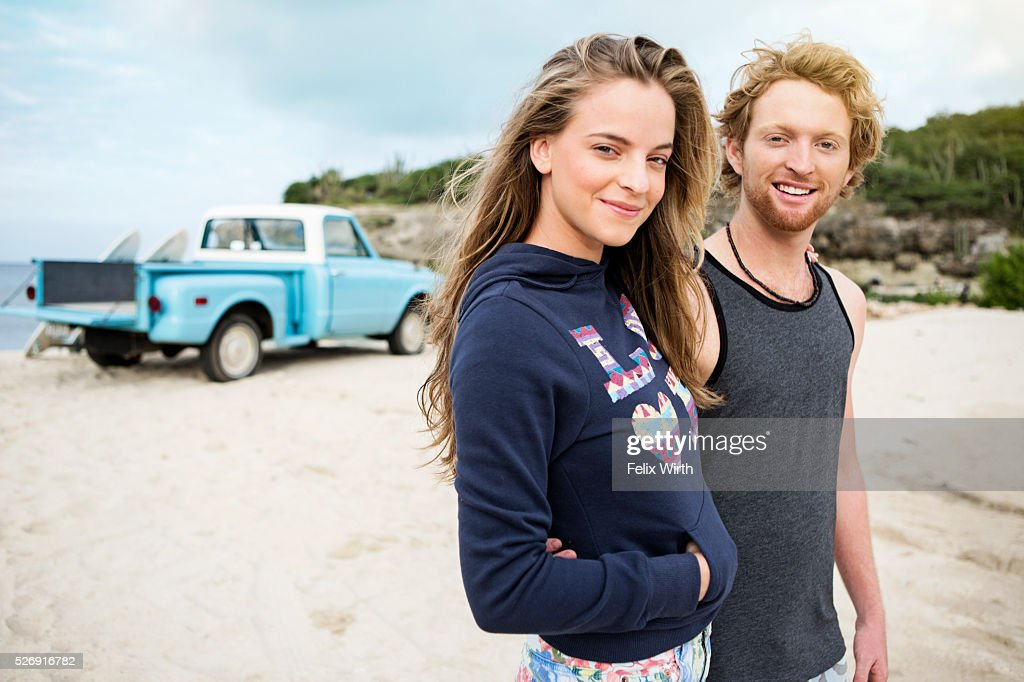 Portrait of couple at beach, with pickup truck in background : Stock Photo