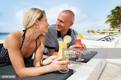 Portrait of couple having drink on deck chair on beach : Foto de stock