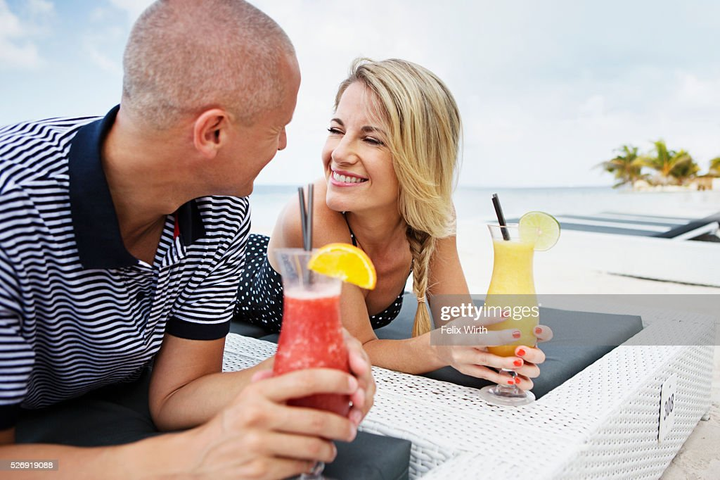 Portrait of couple having drink on deck chair on beach : Stock Photo