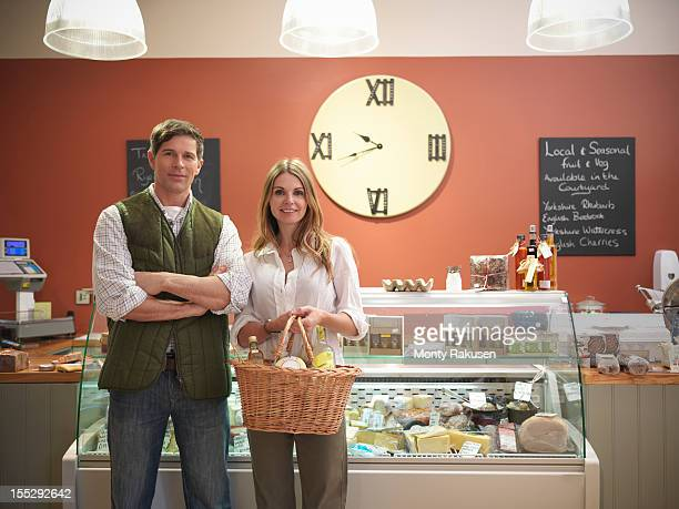 Portrait of couple holding basket in front of delicatessen counter in farm shop with large clock on wall