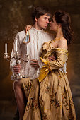 portrait of couple in historical costumes on dark background