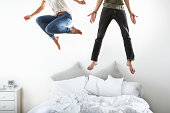 Portrait of couple jumping on bed