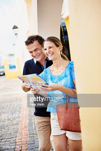 Portrait of couple looking at guidebook : Stock-Foto