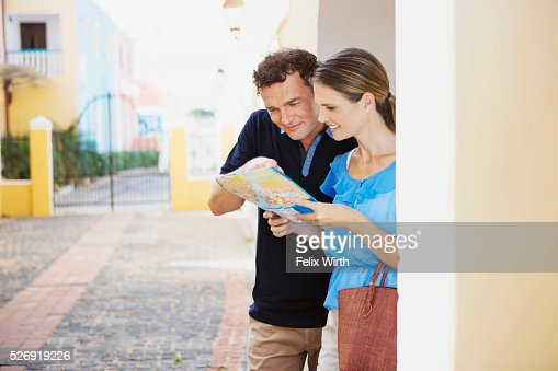 Portrait of couple looking at guidebook : Foto de stock