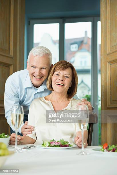 Portrait of couple sitting at table, smiling