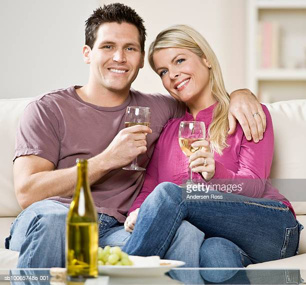 Portrait of couple sitting on couch drinking wine