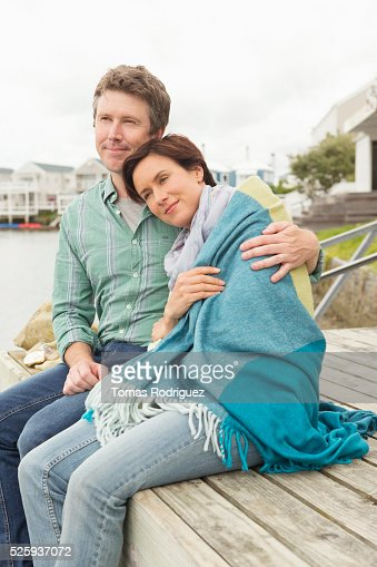 Portrait of couple sitting on pier relaxing : Stock Photo