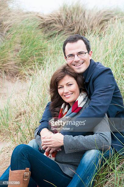 Portrait of couple sitting on sand dune