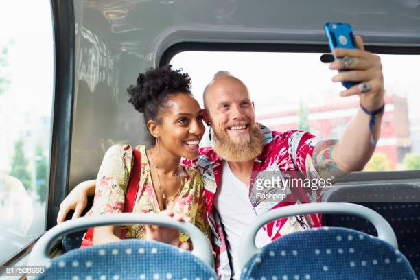 Portrait of couple taking selfies on a bus