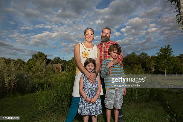 Portrait of couple with children on family herb farm