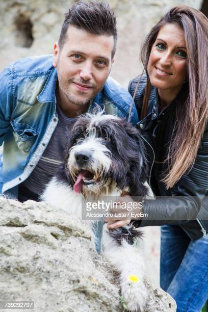 Portrait Of Couple With Dog On Rock