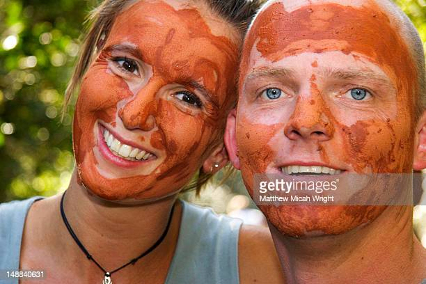 Portrait of couple with faces painted with traditional red soil, mixed with water to protect themselves from evil spirits and sunburn.