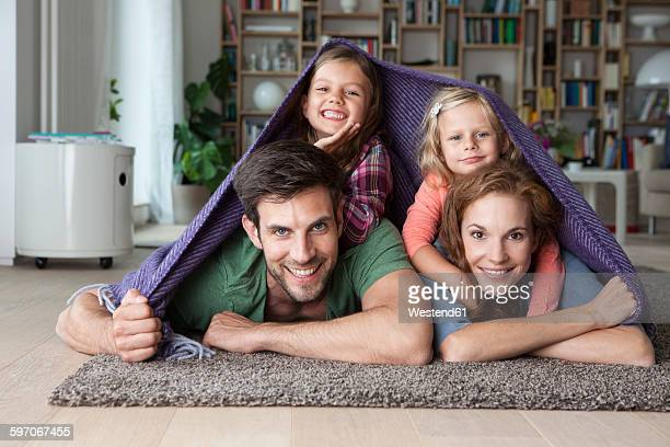 Portrait of couple with her little daughters lying together on the floor of the living room covered by a blanket