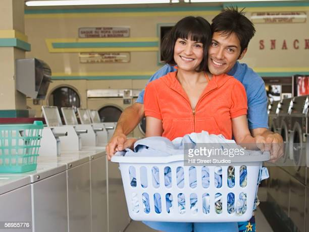 Portrait of couple with laundry hugging at launderette