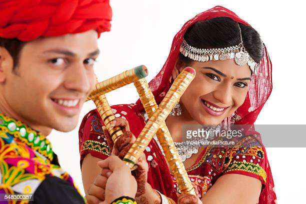 Portrait of couple with sticks dancing