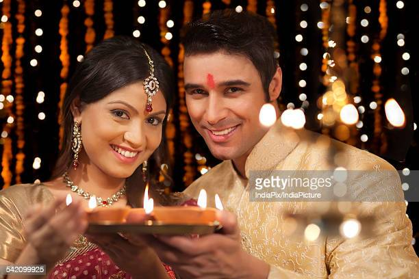 Portrait of couple with tray of diyas