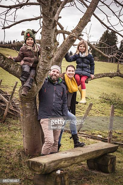 Portrait of couple with two daughters climbing bare tree