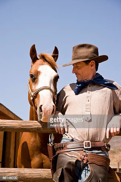 Portrait of cowboy standing next to a horse
