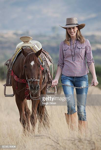 Portrait of cowgirl leading horse