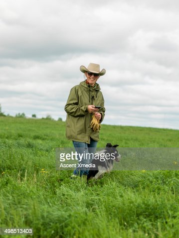 Portrait of cowgirl texting while walking on range : Foto de stock