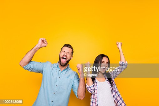 Portrait of crazy man couple full of happiness yelling loudly holding raised arms keeping eyes closed celebrating victory isolated on vivid yellow background : Stock Photo