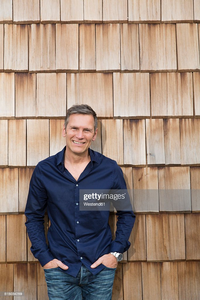 Portrait of creative business man in front of wood shingle panelling