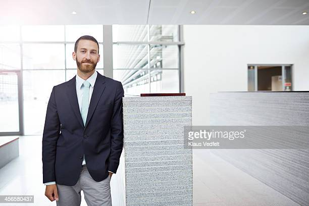 Portrait of creative businessman, standing in hall
